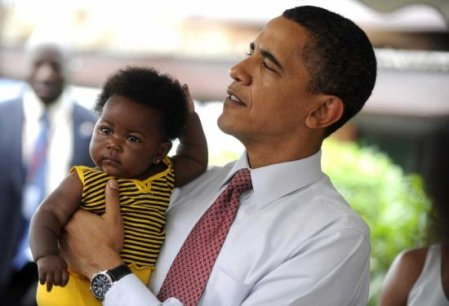 OUR BLACK PRESIDENT OF THE BLACK WORLD HOLDING A BLACK BEAUTY AT LA GENERAL HOSPITAL,ACCRA,GHANA,JULY 11,2009