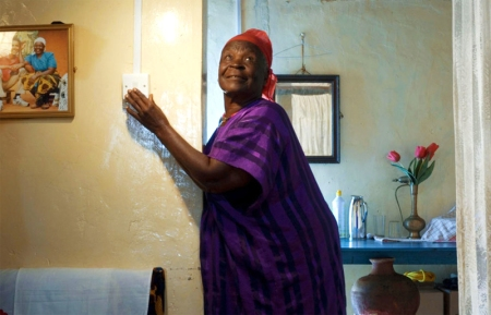 US President Barack Obama's step-grandmother Sarah flicks on the lights on August 19, 2009 after Greenpeace installed a solar power system at her home in Kogelo Village.  The environmentalist group is hosting a workshop on renewable energy in the country drawing youth from Sarah's Kogelo village in western Kenya and the country's largest slum in Nairobi, Kibera.
