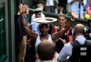 Serena Williams of the United States balances the trophy on her head after winning the women's singles final against Garbine Muguruza of Spain, at the All England Lawn Tennis Championships in Wimbledon, London, Saturday July 11, 2015. (Jonathan Brady/PA via AP)      UNITED KINGDOM OUT      -    NO SALES     -    NO ARCHIVES